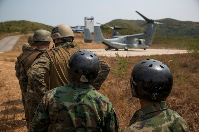 Royal Thai and U.S. Marines wait to board an MV-22B Osprey at Hat Yao, Kingdom of Thailand Feb. 18 during Exercise Cobra Gold 2014. Utilizing joint service and multinational training is vital to maintaining the readiness and interoperability of the Thai, Republic of Korea, U.S. and other participating military forces. The Royal Thai Marines are with Reconnaissance Battalion, Royal Thai Marine Corps Division. The U.S. Marines are with 3rd Reconnaissance Battalion, 3rd Marine Division, III Marine Expeditionary Force.