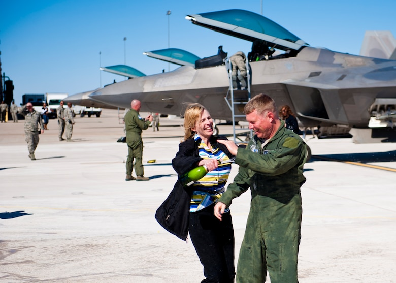 Colonel Andrew Croft, 49th Wing commander, celebrates with his wife, Vicki Croft, after his final flight in the F-22 Raptor at Holloman Ai Force Base, N.M., Feb. 20. The 7th Fighter Squadron and members of the Holloman community celebrated this sortie before the F-22s depart for Tyndall Air Force Base, Fla., in early April. (U.S. Air Force photo by Airman 1st Class Daniel Liddicoet/Released)