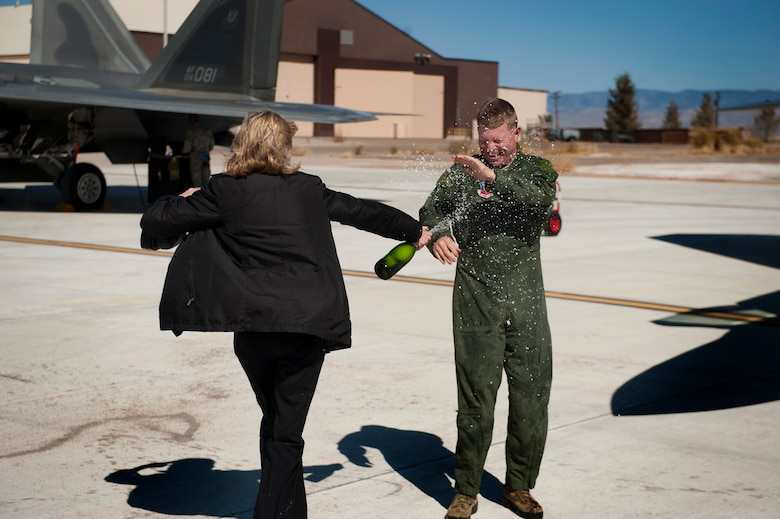Vicki Croft sprays champagne on Col. Andrew Croft, 49th Wing commander, after his final flight in the F-22 Raptor at Holloman Air Force Base, N.M., Feb. 20. The 7th Fighter Squadron and members of the Holloman community celebrated this sortie before the F-22s depart for Tyndall Air Force Base, Fla., in early April. (U.S. Air Force photo by Airman 1st Class Aaron Montoya / Released)