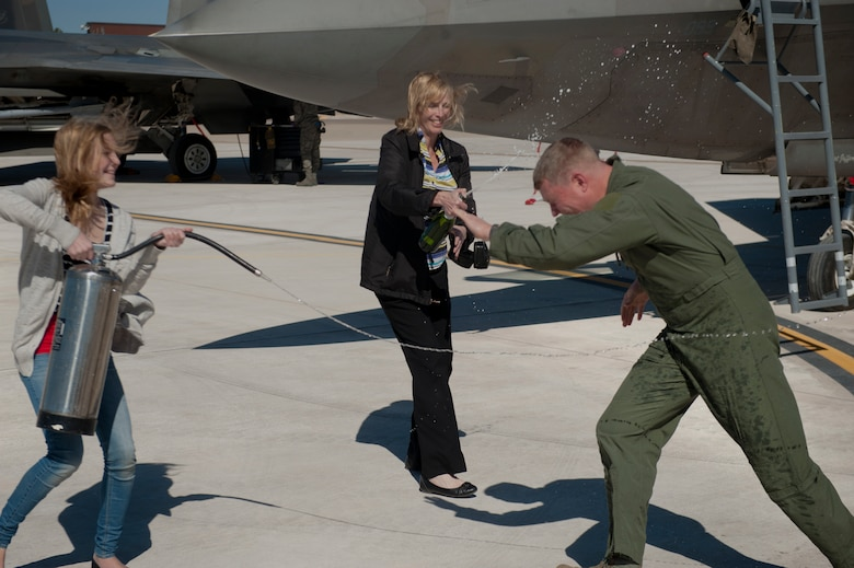 Nicole Croft and Vicki Croft spray Col. Andrew Croft, 49th Wing commander, after landing from the final F-22 Raptor four-ship tactical sortie flown at Holloman Air Force Base, N.M., Feb. 20. The 7th Fighter Squadron and members of the Holloman community celebrated this sortie before the F-22s depart for Tyndall Air Force Base, Fla., in early April. (U.S. Air Force photo by Airman 1st Class Aaron Montoya / Released)