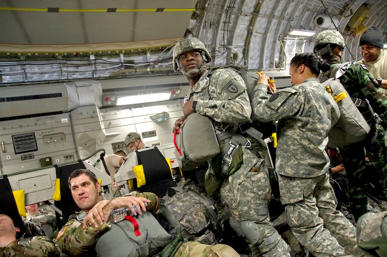 Paratroopers of 4th Infantry Brigade Combat Team (Airborne), 25th Infantry Division, rig and inspect their parachutes during a 17-hour flight in a 517th Airlift Squadron C-17 Globemaster III. The five-ship C-17 formation refueled twice during the trip. (U.S. Air Force photo/Staff Sgt. William Banton)