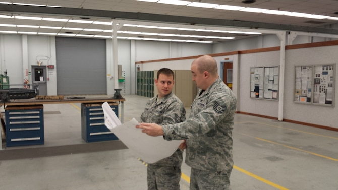 Tech. Sgt. Travis Waskom, aircraft structural maintenance section chief, left, and Tech. Sgt. Steven Farley, assistant section chief, look over plans for placing equipment to create maximum efficiencies in the 552nd Maintenance Squadron's Fabrication Flight after a recent recapitalization provided additional floor space within Bldg. 230. (Air Force photo by Tech. Sgt. Mark Smith)