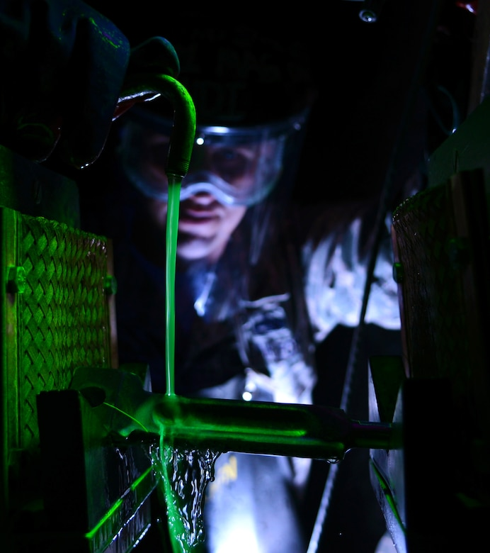 Tech. Sgt. Frank Castonguay pours a fluorescent oil bath over a KC-135 Stratotanker brake key inside a magnetic field generator Feb. 11, 2014, at Royal Air Force Mildenhall, England. The oil bath coats the part in fluorescent particles, which are attracted to any cracks after a magnetic field is established on either end of the part. This method quickly allows non-destructive inspection shop members to identify dangerous defects in parts. Castonguay is a 100th Maintenance Squadron NDI craftsman. (U.S. Air Force photo/Airman 1st Class Dillon Johnston)