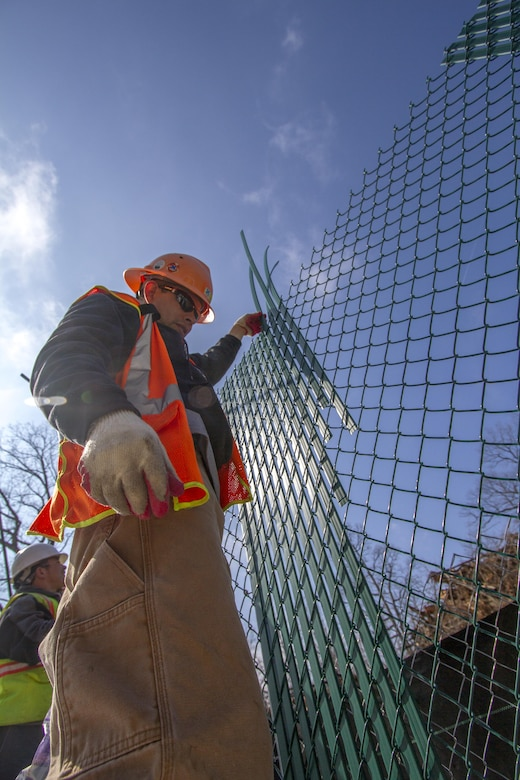ARLINGTON, Va. -- Juan Benavides, a sub-contractor with Hercules Fencing, places privacy slats into fencing that separates the Millennium Project from the rest of Arlington National Cemetery Feb. 19, 2014. Contractors are using the fencing to keep the general public out of the active construction area for the 27-acre project, which will add nearly 30,000 burial and niche spaces with a mix of above-ground columbariums and in-ground burials. The project also involves restoring an impaired stream that runs through the area. (U.S. Army photo/Patrick Bloodgood)