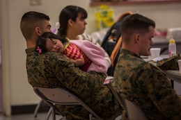 """Cpl. Luis Urquijo soothes his daughter to sleep during a """"P.S., before you say I do"""" seminar at the Blinder Memorial Chapel, Feb. 19. The Naval Hospital Camp Pendleton hosted the seminar to educate Marines, sailors and their significant others about potential stressors and difficulties that could arise during the early stages of marriage. Urquijo is an administrative clerk with Headquarters and Support Battalion."""