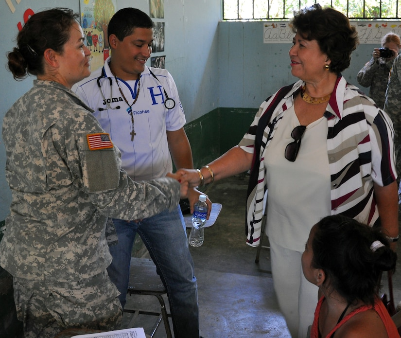 U.S. Army Spc. Lourdes Tarin greets Maria Luisa Martell de Matute, Vice-Mayor of Puerto Cortez during the vice-mayor's visit to an ongoing Medical Readiness and Training Exercise (MEDRETE) being conducted in the town of Caoba, Department of Cortes, Honduras, Feb. 20, 2014.  Several key leaders from Joint Task Force-Bravo met with Honduran military and civic leaders at the site to observe the medical relief mission and engage in discussion on how to build on the strong relationship between the U.S. and Honduras, and how Joint Task Force-Bravo can continue to partner with Honduras in order to provide assistance to those in need.  (U.S. Air Force photo by Capt. Zach Anderson)