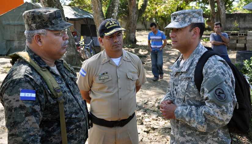 U.S. Army Lt. Col. Frank Melgarejo, Joint Task Force-Bravo Director of Operations, visits with Honduran Army Col. Adolfo Puerto, Chief of Staff of the Honduran 105th Infantry Brigade and Honduran Navy Commander Juan De Jesus during a visit to an ongoing Medical Readiness and Training Exercise (MEDRETE) being conducted in the town of Caoba, Department of Cortes, Honduras, Feb. 20, 2014.  Several key leaders from Joint Task Force-Bravo met with Honduran military and civic leaders at the site to observe the medical relief mission and engage in discussion on how to build on the strong relationship between the U.S. and Honduras, and how Joint Task Force-Bravo can continue to partner with Honduras in order to provide assistance to those in need.  (U.S. Air Force photo by Capt. Zach Anderson)