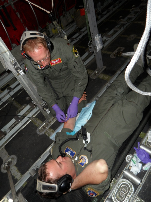 U.S. Air Force Maj. Andrew Allen, 7th Aerospace Medicine Squadron, inserts an intravenous line into Staff Sgt. Nicholas Cardin, 18th Air Evacuation Squadron, during an during in-flight resuscitation training Jan. 10, 2014, at Ross Island, Antarctica. Allen not only provided medical care for aviators, but had primary medical responsibility for all military personnel on station, which includes members of the U.S. Air Force, U.S. Army, U.S. Navy and U.S. Coast Guard. Additionally, he supported casualty evacuation missions and patient movement across the continent. (Courtesy photo)