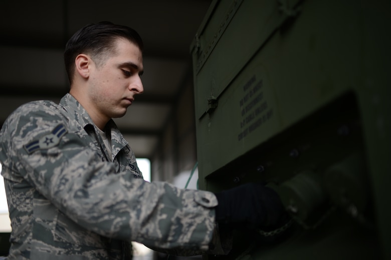 U.S. Air Force Airman 1st Class Christopher Lomelin, 606th Air Control Squadron power production technician from Caredo, Texas, removes the cap of a plug on a generator at Spangdahlem Air Base, Germany, Feb. 20, 2014. The generator can supply satellite equipment power for up to eight continuous hours on one tank of fuel. (U.S. Air Force photo by Senior Airman Gustavo Castillo/Released)