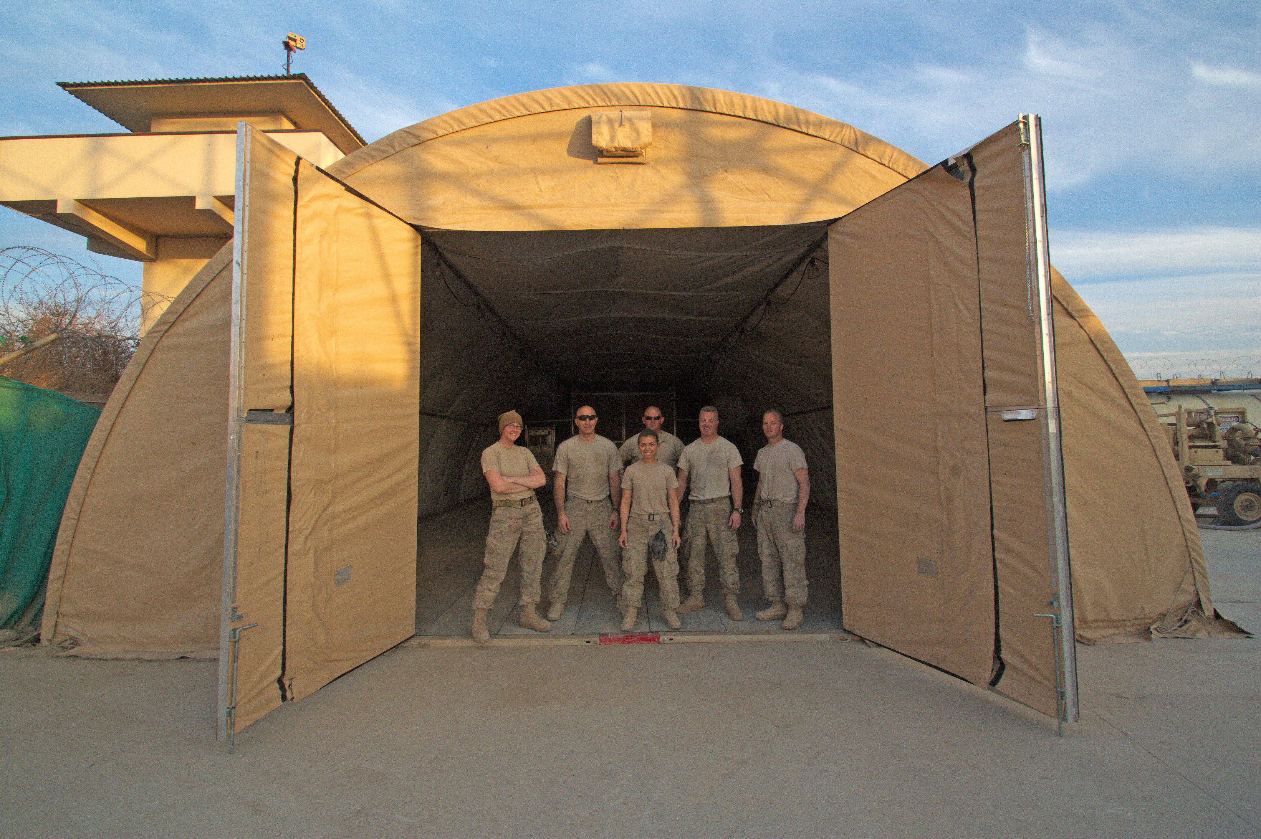 Airmen from the 451st Air Expeditionary Group stand in the entrance of an Alaska tent that ? & Photos