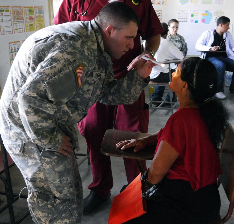 U.S. Army Sgt. Eric Penner examines a Honduran woman during a Medical Readiness Training Exercise (MEDRETE) conducted by Joint Task Force-Bravo's Medical Element (MEDEL) in the village of Kele Kele, Department of Puerto Cortes, Honduras, Feb. 26, 2014.  MEDEL, with support from JTF-Bravo Joint Security Forces, Army Forces Battalion, and the 1-228th Aviation Regiment, partnered with the Honduran Ministry of Health, the Honduran Red Cross, and the Honduran military to provide medical care to more than 1,100 people over two days in Kele Kele and Caoba, two remote villages in the Puerto Cortes region of Honduras.  (Photo by U.S. Army Sgt. Courtney Kreft)