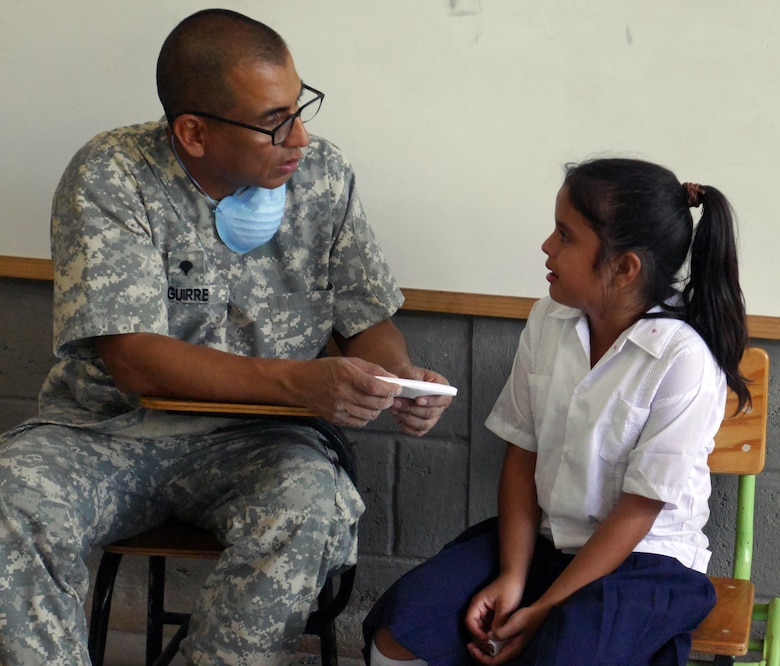 U.S. Army Spc. Harold Aguirre comforts a young Honduran child after a dental procedure during a Medical Readiness Training Exercise (MEDRETE) conducted by Joint Task Force-Bravo's Medical Element (MEDEL) in the village of Kele Kele, Department of Puerto Cortes, Honduras, Feb. 26, 2014.  MEDEL, with support from JTF-Bravo Joint Security Forces, Army Forces Battalion, and the 1-228th Aviation Regiment, partnered with the Honduran Ministry of Health, the Honduran Red Cross, and the Honduran military to provide medical care to more than 1,100 people over two days in Kele Kele and Caoba, two remote villages in the Puerto Cortes region of Honduras.  (Photo by U.S. Army Sgt. Courtney Kreft)