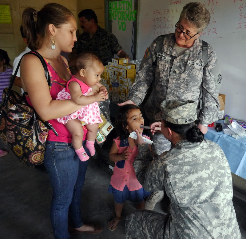 U.S. Army Sgt. Michelle Krieg and U.S. Army Sgt. Melissa Woods administer medication to a Honduran child during a Medical Readiness Training Exercise (MEDRETE) conducted by Joint Task Force-Bravo's Medical Element (MEDEL) in the village of Kele Kele, Department of Puerto Cortes, Honduras, Feb. 26, 2014.  MEDEL, with support from JTF-Bravo Joint Security Forces, Army Forces Battalion, and the 1-228th Aviation Regiment, partnered with the Honduran Ministry of Health, the Honduran Red Cross, and the Honduran military to provide medical care to more than 1,100 people over two days in Kele Kele and Caoba, two remote villages in the Puerto Cortes region of Honduras.  (Photo by U.S. Army Sgt. Courtney Kreft)