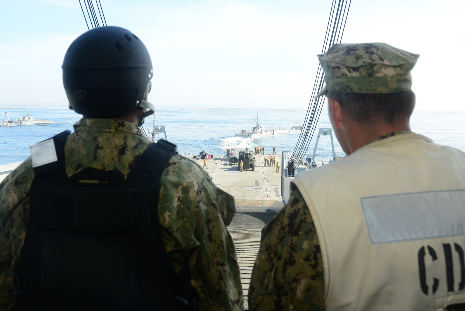 Rear Adm. Frank Ponds, commander of Expeditionary Strike Group Three, and Capt. Kevin Flanagan, commander of Naval Beach Group One, observe Improved Navy Lighterage System (INLS) Causeway Ferry 17 detach from the INLS Roll-on/Roll-off Discharge Facility during exercise Brilliant Scepter 2014. Brilliant Scepter 2014 is an exercise providing ship-to-shore transportation of combat cargo for Navy amphibious forces and the Marine Corps. (U.S. Navy photo by Mass Communication Specialist 2nd Class Scott Bigley/Released)