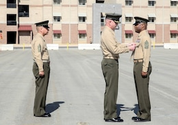 Lieutenant Col. John O'Neal, center, commanding officer, 15th Marine Expeditionary Unit, pins the Legion of Merit Medal on Sgt. Maj. John Scott, right, during a relief and appointment ceremony aboard Camp Pendleton, Calif., Feb. 21, 2014. Scott will be taking charge as the senior enlisted advisor to Marine Corps Forces Special Operations Command, Camp Lejeune, N.C. (U.S. Marine Corps photo by Cpl. Emmanuel Ramos/Released)