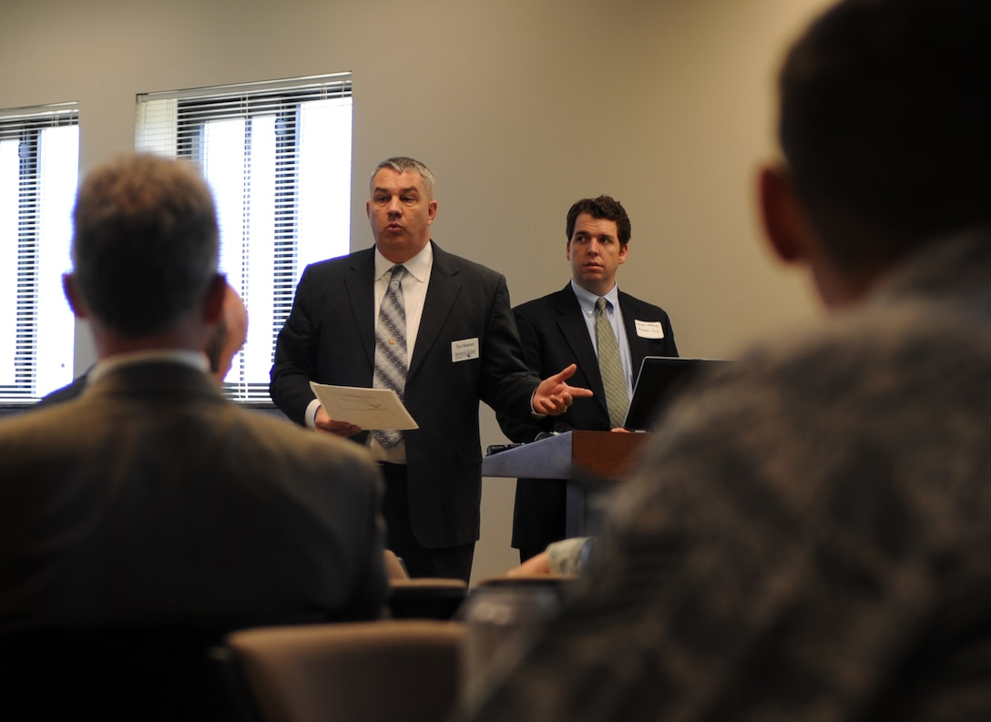 Don Noonan, Marstel-Day lead facilitator, left, and James McMurray, a Marstel-Day facilitator, brief the meeting attendees on breaking up into work groups Feb. 21, 2014, at the chapel Fellowship Hall on Buckley Air Force Base, Colo. Groups discussed the upcoming joint shooting range and plans for base trails. This is just one of numerous actions taken toward the Public-Public & Public-Private, or P4, initiative.  (U.S. Air Force photo by Airman Emily E. Amyotte/Released)