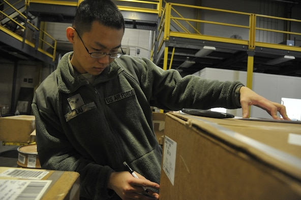 Airman 1st Class Bing Liu, 509th Logistics Readiness Squadron transportation management apprentice, inspects information on a box at Whiteman Air Force Base, Mo., Feb. 5, 2014. This process is done to confirm the information is accurate and the property is delivered to its destination. (U.S. Air Force photo by Airman 1st Class Keenan Berry/Released)