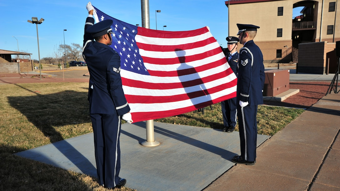 """Honor guardsmen from the 27th Special Operations Wing prepare to fold the flag during a memorial ceremony Feb. 18, 2014 at Cannon Air Force Base, N.M. The ceremony was conducted in honor of Capt. Ryan Hall, Capt. Nicholas Whitlock, 1st Lt. Justin Wilkens and Senior Airman Julian Scholten, the aircrew members who lost their lives when """"Ratchet 33"""", a U-28A, crashed in Djibouti, Africa, Feb. 18, 2012. (U.S. Air Force photo/Senior Airman Whitney Amstutz)"""