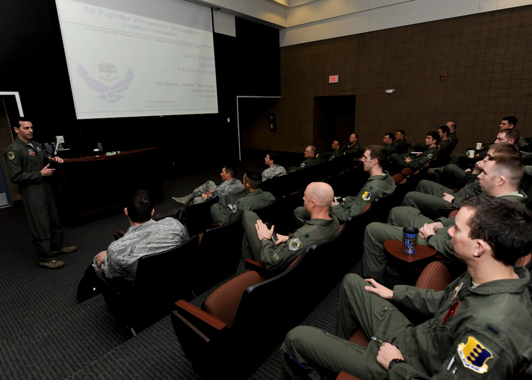 Maj. Shane Marchand, 86th Fighter Weapons Squadron project officer, briefs B-1 aviators from the 34th Bomb Squadron in preparation for the Combat Hammer exercise at Ellsworth Air Force Base, S.D., Feb. 17, 2014. As part of his role as combat hammer lead, Marchand traveled from Eglin AFB, Fla., to review the details and objectives of the exercise, emphasizing the importance of safety and remaining focused. (U.S. Air Force photo by Senior Airman Anania Tekurio/Released)