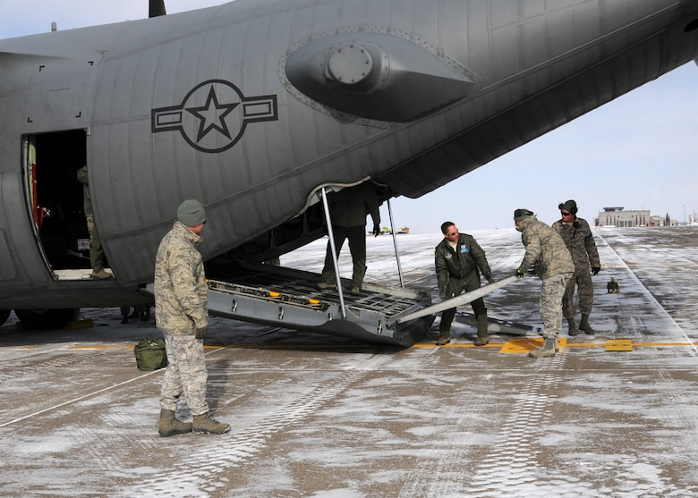 Members of the Wyoming Air National Guard set the ramps to unload a truck from a C-130 at the 120th Fighter Wing Feb. 8, 2014.  National Guard photo/2nd Lt. Robin Jirovsky.