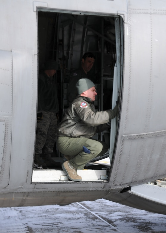 A member of the Wyoming Air National Guard manually opens the cargo door of a C-130 to unload a truck in preparation for aerial port training Feb. 8, 2014 at the 120th Fighter Wing.  National Guard photo/2nd Lt. Robin Jirovsky.