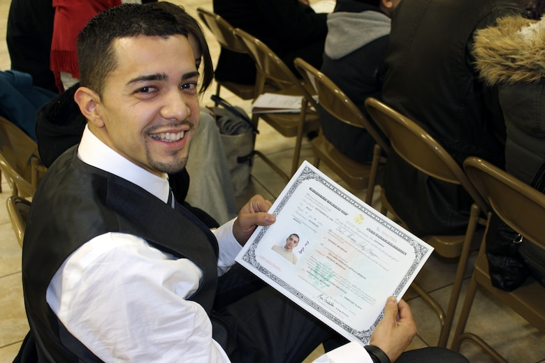131218-Z-VA676-009 – Airman 1st Class Eduardo Arteaga shows off the certificate which declares him to be an American citizen, just moments after taking the Oath of Allegiance to the United States during a ceremony on Feb. 18, 2014. Arteaga recently joined the Michigan Air National Guard's 127th Wing, which helped to facilitate his quest to become a U.S. citizen. The photo of Arteaga on the certificate was taken while Arteaga was at Basic Military Training. (U.S. Air National Guard photo by TSgt. Dan Heaton / Released)
