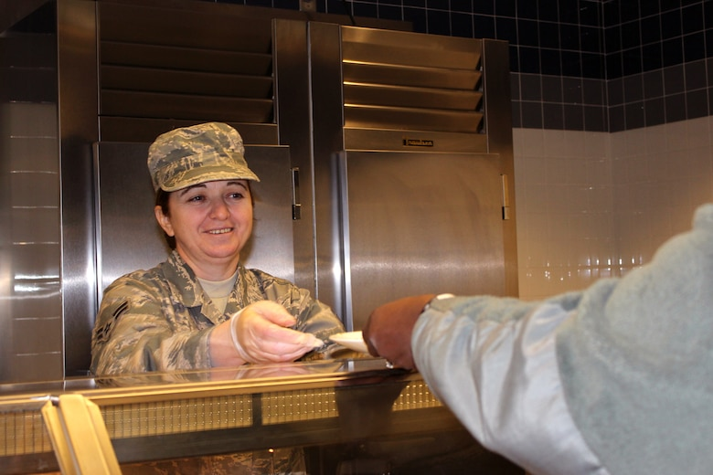 140208-Z-VA676-079 -- Airman 1st Class Elvira Shani serves an Airman during lunch at the Dining Facility at Selfridge Air National Guard Base, Mich., Feb. 8, 2014. Shani, a native of Albania, joined the Air National Guard on the day before her 40th birthday – the last day she was eligible to join – as a way to say thank you to America for the opportunities she has found since to immigrated to the U.S. about 10 years ago. (U.S. Air National Guard photo by TSgt. Dan Heaton / Released)