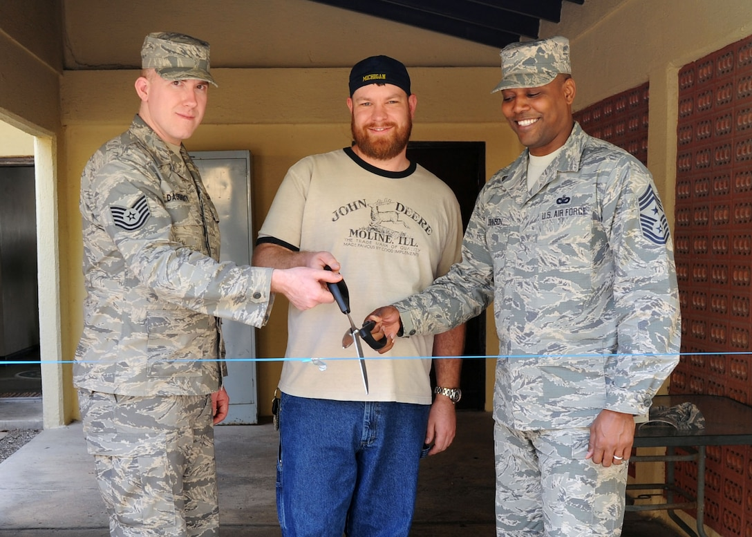 INCIRLIK AIR BASE, Turkey –Tech. Sgt. Kenneth Daugherty (left) 39th Communications Squadron NCO in charge of network management, Adam Ewalt, and Chief Master Sgt. Anthony Johnson, 39th Air Base Wing command chief, cut a ribbon to commemorate the opening of the Incirlik Air Base, Turkey Airmen's Attic Feb. 18. Daughery and Ewalt are part of group of volunteers that stepped up and stepped in to action dedication over 100 hours of volunteer service to establish an Airmen's Attic here. The team stepped up and stepped into action dedication over 100 hours of volunteer service to establish an Airmen's Attic here (U.S. Air Force photo by Staff Sgt. Veronica Pierce/Released)