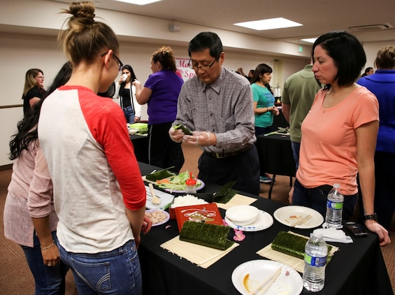 Keijiro Akiyama, owner of Akiyama Sushi, shows spouses how to make Norimaki sushi during a sushi making class hosted by the Marauders Spouse Club, Feb. 22, 2014, aboard Marine Corps Air Station Iwakuni, Japan. Akiyama brought other forms of sushi for the attendees to enjoy before the class began.