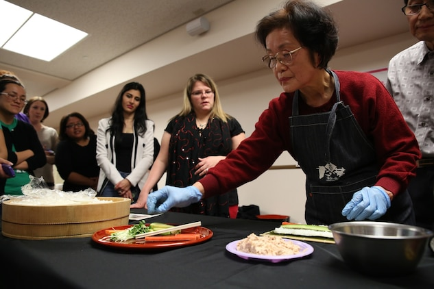 Michiyo Okazaki, a Japanese volunteer, demonstrates how to make Norimaki during a sushi making class hosted by the Marauders Spouse Club, Feb. 22, 2014, aboard Marine Corps Air Station Iwakuni, Japan. The Marauders Spouse Club offered the class to spouses and guests from all units aboard station.