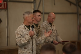 "Jacob Schlauder, center, a corpsman with 1st Battalion, 9th Marine Regiment, is about to be awarded the Navy and Marine Corps Commendation Medal with a combat distinguishing device before a town hall meeting aboard Camp Leatherneck, Helmand province, Afghanistan, Feb. 18, 2014.  General Amos personally presented the medal with combat ""V"" to Schlauder, who despite suffering injuries himself, rendered medical aid to Marines who were injured in an attack when their vehicle was struck by an armor-piercing, rocket-propelled grenade while on patrol Jan. 25, 2014."