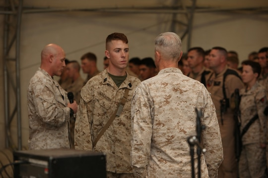 "Seaman Jacob Schlauder, center, a corpsman with 1st Battalion, 9th Marine Regiment, stands before Gen. James F. Amos, commandant of the Marine Corps, as Sgt. Maj. Micheal P. Barrett, sergeant major of the Marine Corps, reads Schlauder's Navy and Marine Corps Commendation Medal with a combat distinguishing device citation at a town hall meeting aboard Camp Leatherneck, Helmand province, Afghanistan, Feb. 18, 2014. General Amos personally presented the medal with combat ""V"" to Schlauder, who despite suffering injuries himself, rendered medical aid to Marines who were injured in an attack when their vehicle was struck by an armor-piercing, rocket-propelled grenade while on patrol Jan. 25, 2014."