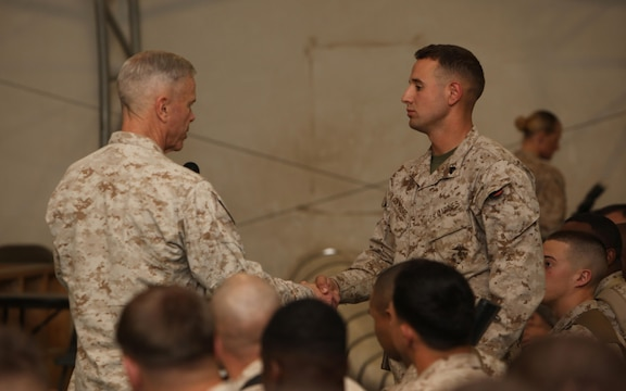 General James F. Amos, commandant of the Marine Corps, shakes hands with and thanks a Marine for asking the first question during a town hall meeting aboard Camp Leatherneck, Helmand province, Afghanistan, Feb. 18, 2014. General Amos and Sgt. Maj. Micheal P. Barrett, sergeant major of the Marine Corps, visited with Marines and sailors of Regional Command (Southwest) to speak about the peacetime Marine Corps force and the reawakening of the Corps.
