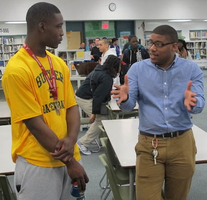 Justin Colar, civil engineer, Huntsville Center's Engineering Directorate, mentors a student during the STEM outreach event at Butler High School Feb. 20.