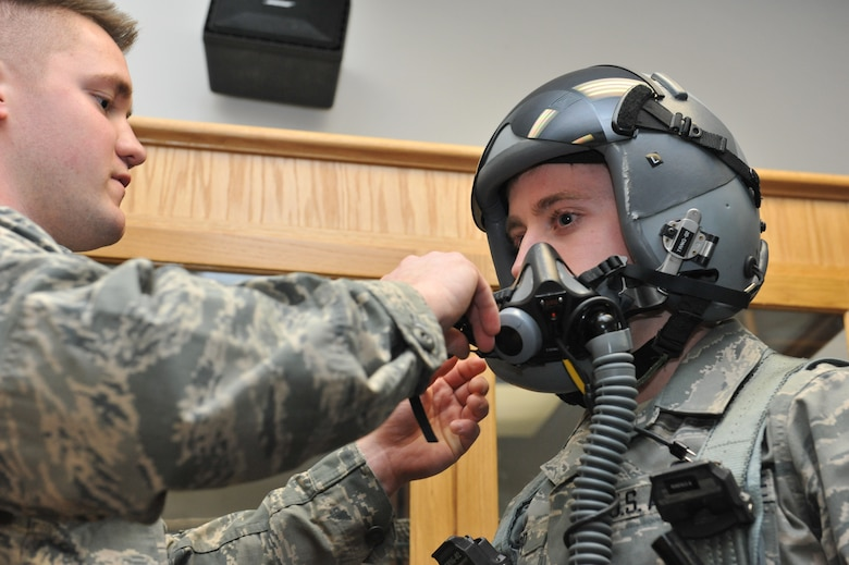Airman 1st Class Anthony Patterson and Airman 1st Class Adam Clapp, 509th Operations Support Squadron aircrew flight equipment technicians, demonstrate how to fit a pilots helmet and MBU-20/P soft shell mask. The mask provides oxygen to the pilot while flying at high altitudes. (U.S. Air Force photo by Airman 1st Class Joel Pfiester/Released)