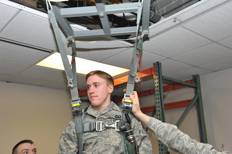 Airman First Class Adam Clapp, 509th Operations Support Squadron aircrew flight equipment technician, demonstrates hanging harness training at Whiteman Air Force Base Mo., Feb. 12, 2014. The training is used to simulate a situation when a pilot or aircrew member's parachute gets caught on telephone wires or trees. (U.S. Air Force photo by Airman 1st Class Joel Pfiester/Released)