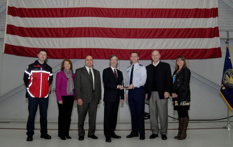 Standing with staff members of the Portland of Portland, Col. Rick Wedan, 142nd Fighter Wing Commander, and Bill Wyatt Executive Director for the Port of Portland, hold the award for the Oregon Air National Guard Employer of the Year award for 2013 during a ceremony at the Portland Air National Guard Base, Ore., Feb., 2014. (Air National Guard photo by Tech. Sgt. John Hughel, 142nd Fighter Wing Public Affairs/Released)