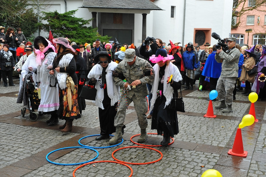 """Senior Airman Urzus Gange, an engine supply technician from 52nd Logistics Readiness Squadron, is guided through hoops by female Bitburg citizens during a Fashing event at Bitburg, Germany, Feb. 16, 2012. During the German holiday tradition, Spangdahlem Airmen participate in the event by keeping the city's ceremonial key away from the Fashing """"fool ladies."""" (U.S. Air Force photo Airman 1st Class Dillon Davis / Released)"""