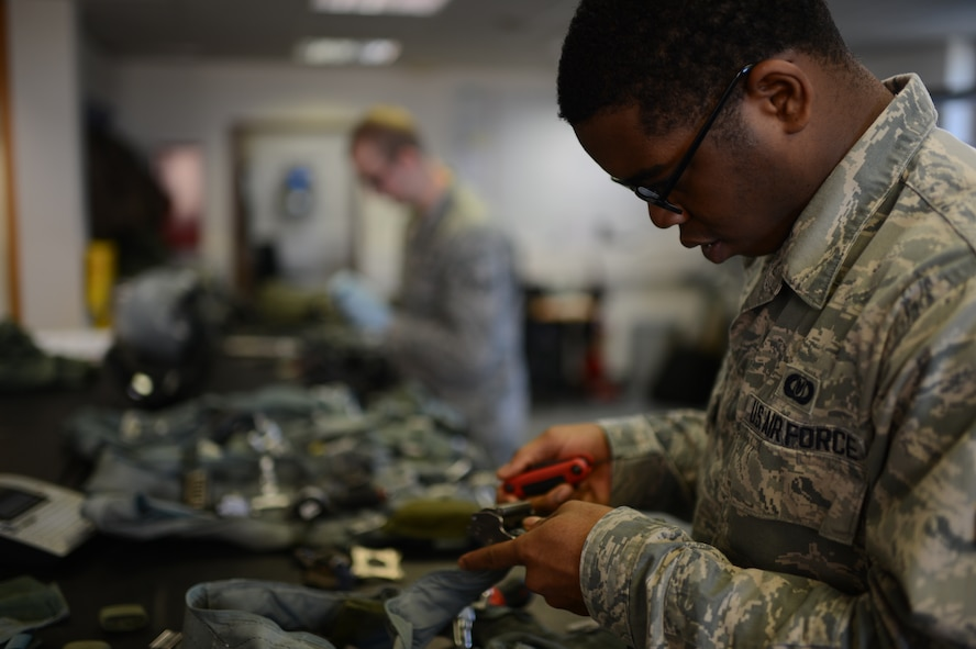 U.S. Air Force Airman 1st Class Stefon Newton, 52nd Operations Support Squadron aircrew flight equipment technician from Shreveport, La., dismantles a restraint harness at Spangdahlem Air Base, Germany, Feb. 24, 2014. The harness connects the pilot to the parachute and survival kit for use in case of in-flight emergencies and must be serviced every 30 days. (U.S. Air Force photo by Senior Airman Gustavo Castillo/Released)