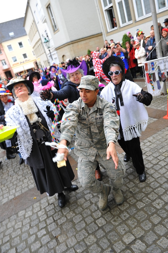"""Senior Airman Urzus Gange, an engine supply technician from 52nd Logistics Readiness Squadron, runs through a street chased by female Bitburg citizens as part of a German tradition during a Fashing event at Bitburg, Germany, Feb. 16, 2012. During the German holiday tradition, the mayor of Bitburg invited a delegation from Spangdahlem Air Base to help him defend the city hall and its ceremonial key from the Fashing """"fool ladies."""" (U.S. Air Force photo Airman 1st Class Dillon Davis / Released)"""