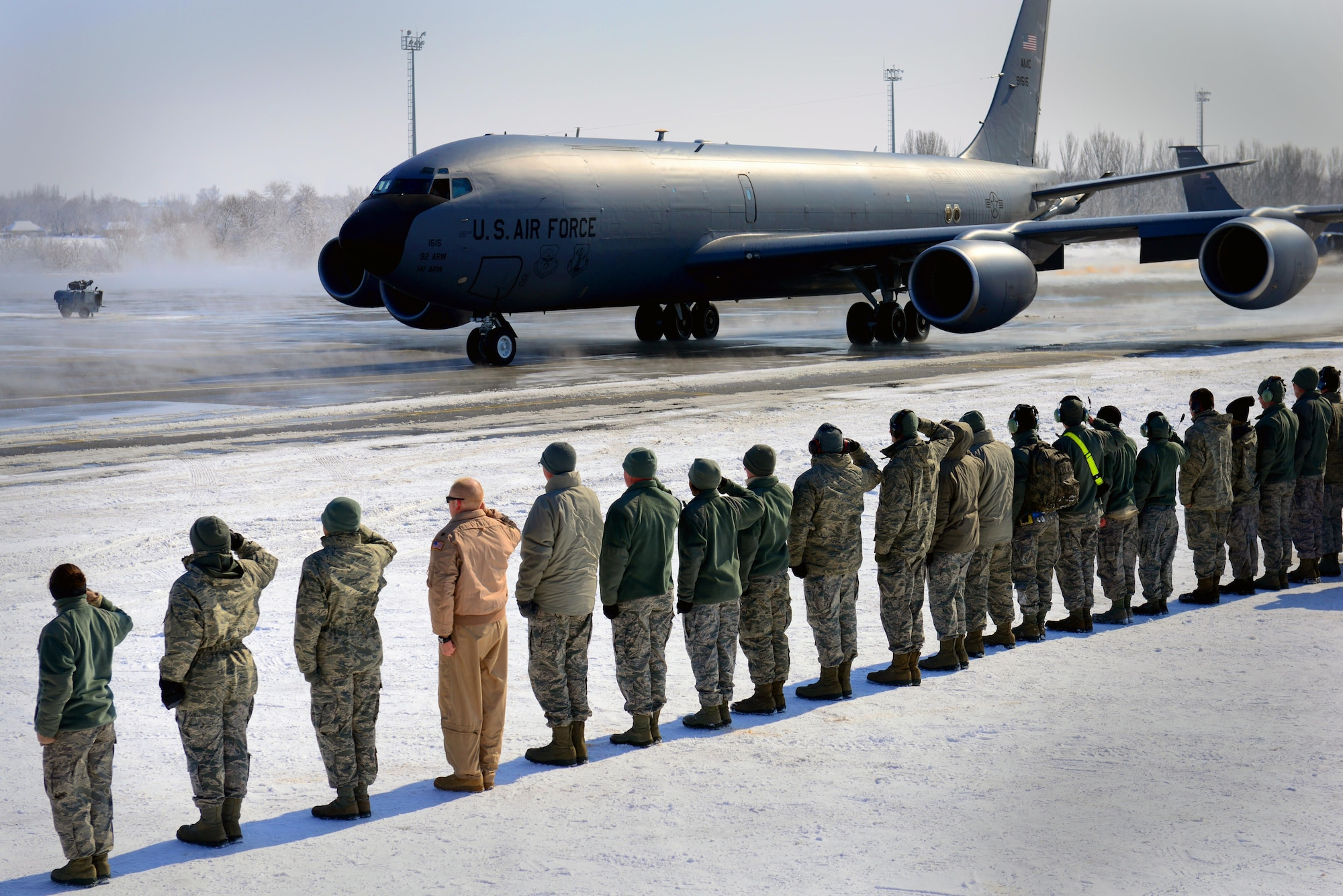 As a KC-135 Stratotanker taxis, the members of the 376th Air Expeditionary Wing salute Feb. 24, 2014, at Transit Center at Manas, Kyrgyzstan. The KC-135 departed the after the final refueling mission over Afghanistan from the Transit Center. (U.S. Air Force photo/Staff Sgt. Travis Edwards)