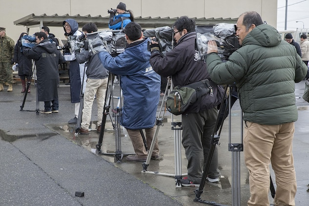 Cameramen from Japanese media outlets record part of the relocation process during a tour aboard Marine Corps Air Station Iwakuni, Japan, Feb. 14, 2014.