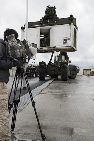 A cameraman from a Japanese media outlet records the relocation process during a tour aboard Marine Corps Air Station Iwakuni, Japan, Feb. 14, 2014. More than 20,000 items had to be moved from the old Marine Aviation Logistics Squadron 12 facilities to their new ones.