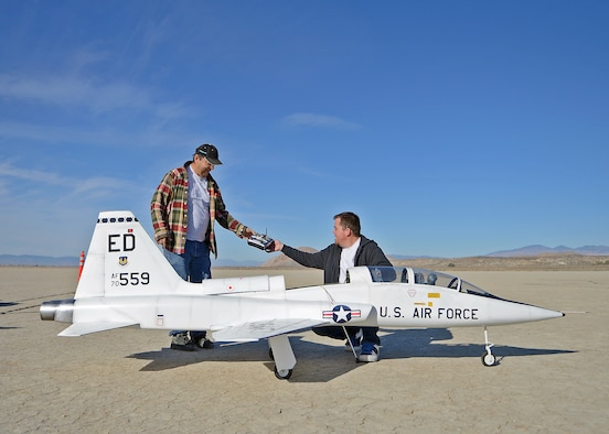 Rodger Hecht hands his son, Brent, a radio-controlled transmitter prior to flying their 12-foot long T-38 Talon R/C replica on the Rosamond Dry Lakebed Feb. 22, 2014. Rodger and Brent started flying R/C models with the Muroc Model Masters R/C Club nearly 20 years ago and decided to build their T-38 with an 82-inch wingspan. The fully-functional model weighs approximately 45 pounds, has two 5-inch electric ducted fans powered by brushless motors and is made of blue foam, carbon fiber, fiber glass, balsa wood and plywood. (U.S. Air Force photo by Jet Fabara)