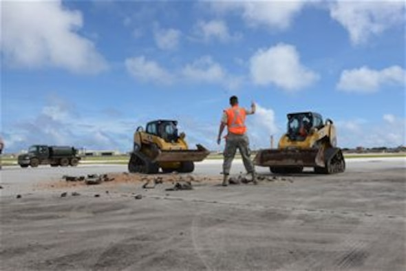 Staff Sgt. Austin Winegardner, 36th Civil Engineer Squadron project leader, directs Airmen operating heavy machinery to clear debris away from a simulated damaged area created during airfield damage repair training on the Andersen Air Force Base, Guam, flightline Jan. 23, 2014. The 36th Civil Engineer Squadron Airmen were the first in the Air Force to receive training on a new airfield damage repair capability.  (U.S. Air Force photo by Airman 1st Class Emily A. Bradley/Released)