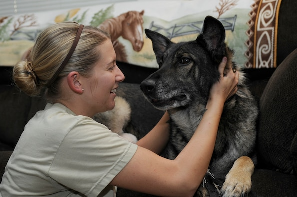 U.S. Air Force Staff Sgt. Alexandra Springman, 355th Security Forces Squadron military working dog handler, pets Dexter, a retired MWD, in Tucson, Ariz., Feb. 25, 2014. Springman adopted Dexter after he retired for the Air Force due to a medical condition. (U.S. Air Force photo by Airman 1st Class Betty R. Chevalier/Released)