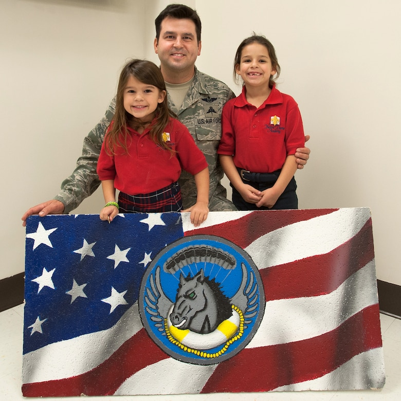 """Master Sgt. Joey Youdell, a pararescueman in the Kentucky Air National Guard's 123rd Special Tactics Squadron, created a """"unit pride"""" ceiling tile with his daughters, Olivia (left) and Juliet. The hand-painted tile is one of several that have been installed in The Winner's Circle recreation center at the Kentucky Air Guard Base in Louisville, Ky. (U.S. Air National Guard photo by Maj. Dale Greer)"""