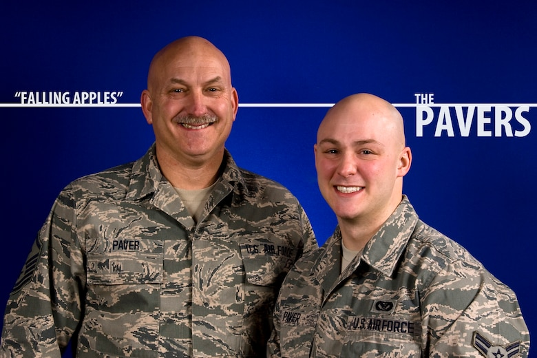 """U.S. Air Force Master Sgt. Wesley F. Paver, 182nd Mission Support Group first sergeant, and Airman 1st Class Jared A. Paver, fire protection specialist with the 182nd Civil Engineer Squadron, are seen together at the 182nd Airlift Wing in Peoria, Ill., Feb. 24, 2014. While one is approaching retirement and the other is just beginning his career, the father and son serve together in Illinois Air National Guard. They are one of several families featured in the wing's ongoing """"Falling Apples"""" series highlighting parents and children Air National Guardsmen. (U.S. Air National Guard photo illustration by Staff Sgt. Lealan Buehrer/Released)"""