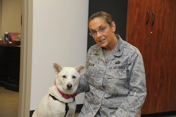 Air Force Col. Ramona Dolson, Air Force Personnel Center chief selection board secretariat, and her dog Bebe pose for a photo Feb. 7 at Joint Base San Antonio-Randolph.  (U.S. Air Force photo by Joel Martinez and photo illustration by Maggie Armstrong)