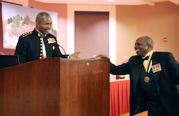 Lt. Gen. Ronald L. Bailey receives a donation toward the Montford Point Marines Memorial Project during  the Montford Point Marine Association's 26th annual Heritage Dinner Dance at the Marston Pavilion aboard Marine Corps Base Camp Lejeune, Feb. 22. More than $2,000 was donated during the event.
